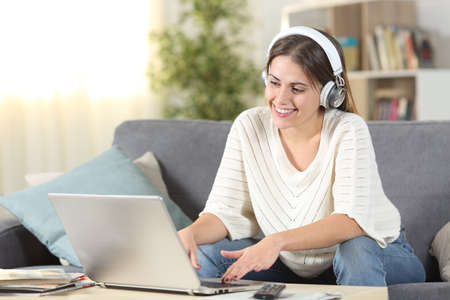 Happy female e-learning using headphones and laptop sitting on a couch in the living room at home