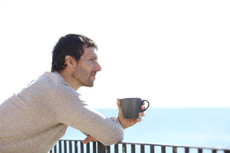 Side view portrait of a serious man holding mug contemplating views from a balcony Stockfoto