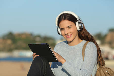 Happy student e-learning wearing headphones and holding a tablet looking at camera