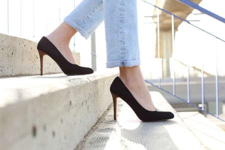 Vista lateral de cerca de las piernas de una mujer con tacones caminando por las escaleras