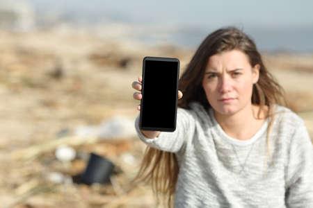 Volunteer showing smart phone blank screen in a dirty beach