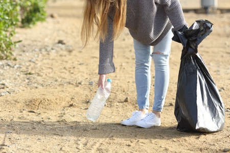 Volunteer cleaning collecting plastic bottle from the ground in a park Imagens