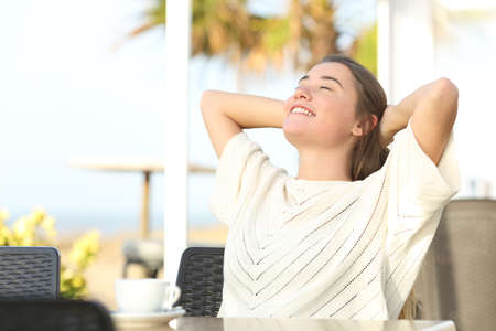 Happy girl relaxing sitting in a hotel terrace on the beach with arms on head