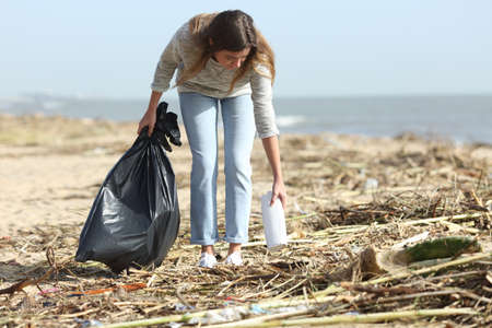 Young volunteer cleaning a dirty beach collecting plastics after storm Imagens