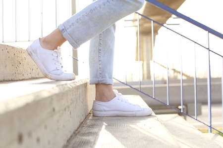 Profile close up of woman legs wearing sneakers walking down stairs