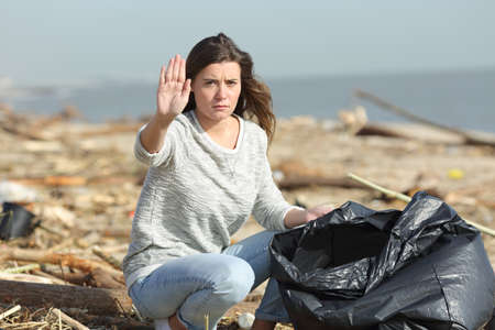 Angry volunteer cleaning a dirty beach gesturing stop with hand looking at camera