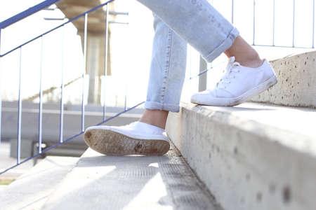 Bliska portret dziewczyny nogi z trampkami schodząc po schodach i zwichnięta kostka