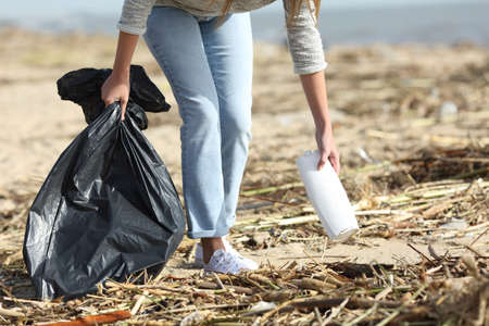 Close up of a volunteer cleaning a dirty beach collecting plastics after storm Imagens