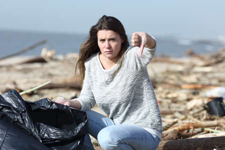 Angry volunteer cleaning a dirty beach gesturing thumbs down looking at camera Imagens
