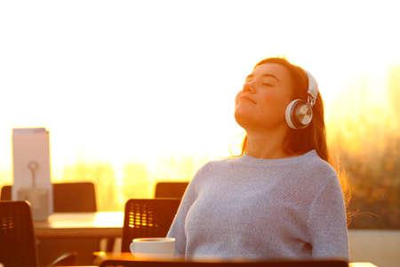 Ragazza rilassata che ascolta musica che indossa le cuffie seduta su una terrazza al tramonto