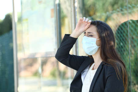 Woman wearing a protective mask complaining suffering head ache in a bus stop
