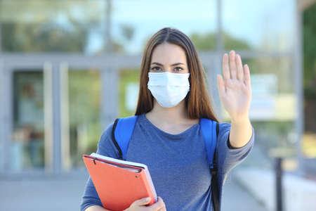 Vista frontal de un estudiante con una máscara protectora gesticulando parada en un campus universitario Foto de archivo