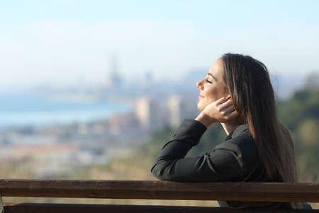 Seitenansichtporträt einer Geschäftsfrau, die sich entspannt auf einer Bank mit geschlossenen Augen und einer Stadt im Hintergrund sitzt Standard-Bild