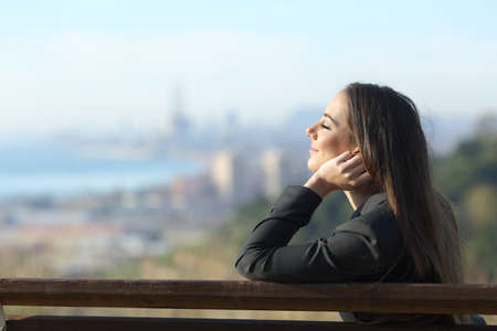 Side view portrait of a businesswoman relaxing sitting on a bench with eyes closed and a city in the background