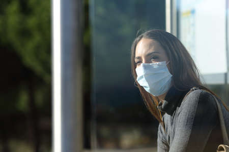Woman wearing a protective mask to prevent virus contagion waiting in a bus stop Фото со стока - 139894326
