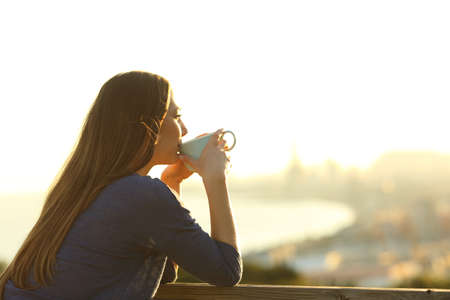 Happy girl drinking coffee contemplating views from a balcony at sunset