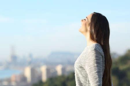 Happy woman breathing fresh air outdoors with a city in the background a sunny day