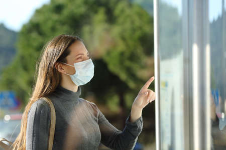 Casual woman wearing a protective mask checking schedule standing in a bus stop