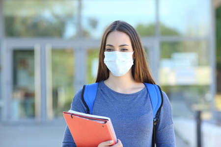 Front view of a student wearing a protective mask walking in a campus Stock Photo