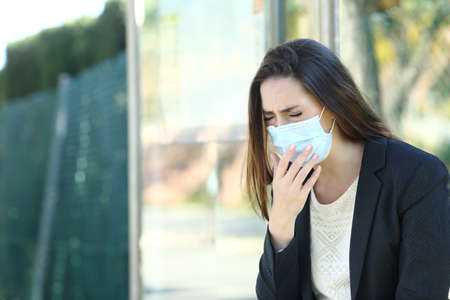 Infected woman wearing a protective mask coughing waiting in a bus stop Фото со стока