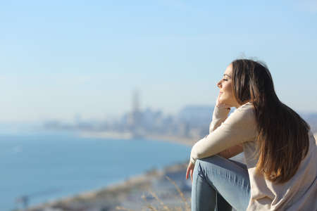 Side view portrait of a woman meditating relaxing sitting outdoors with a coast city in the background