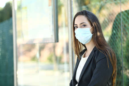 Woman wearing a mask to prevent contagion sitting in a bus stop waiting for transport Фото со стока - 139894409