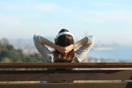 Back view of a woman relaxing listening to music sitting on a bench with a city in the background