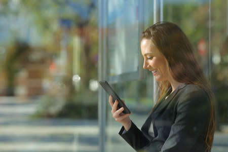 Side view portrait of an executive checking smart phone content waiting in a bus stop