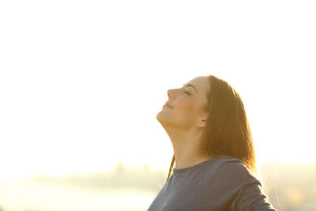 Satisfied woman breathing fresh air standing outdoors at sunset