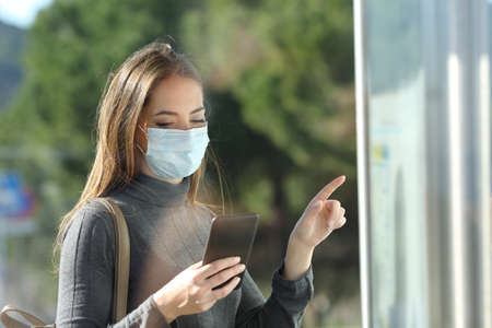 Commuter with a protective mask avoiding contagion checking bus schedule 스톡 콘텐츠