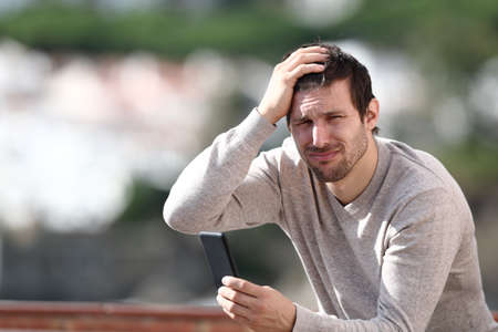 Confused man holding mobile phone complaining after mistake sitting in a rural town