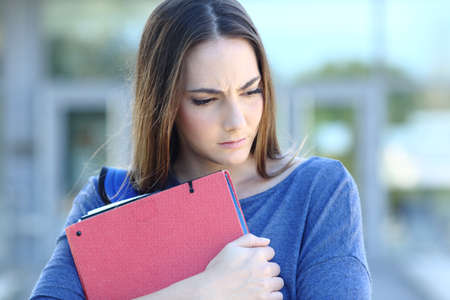 Front view portrait of a sad student looking down embracing folders walking in a college