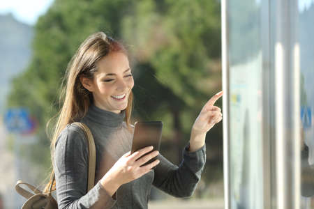 Happy commuter checks smart phone and schedule table waiting for transport in a bus stop 스톡 콘텐츠