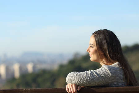 Side view portrait of a satisfied woman contemplating views sitting on a bench