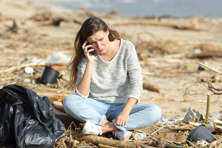 Worried volunteer cleaning a dirty beach calling on phone  sitting on the sand