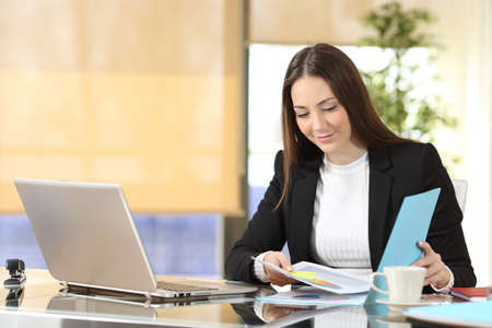 Serious executive checking paper documents sitting at office