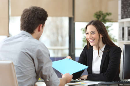 Employee giving folder to his happy manager during interview at office
