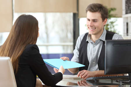 Businessman giving documents to a client sitting at office during an interview Foto de archivo
