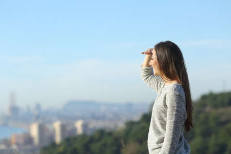 Profile of a happy woman looking at horizon protecting from the sun with hand