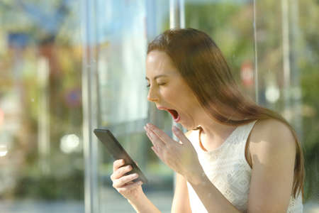 Tired woman yawning checking mobile phone sitting at bus stop waiting for transport
