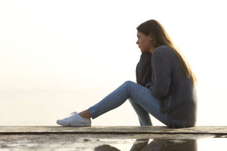 Side view portrait of a sad girl looking away alone sitting outdoors contemplating horizon