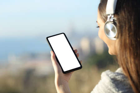 Woman wearing headphones showing and using blank phone screen outdoors