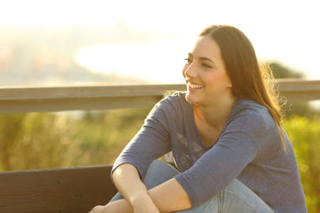 Happy woman smiling and relaxing sitted on a bench with views on the background Stock Photo