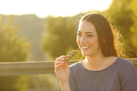 Happy woman eating a cereal bar sitting on a bench at sunset in a park