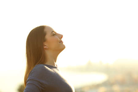 Side view portrait of a single woman breathing deeply fresh air at sunset Standard-Bild
