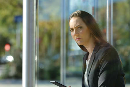 Annoyed business woman holding a phone and waiting at the bus stop looking away
