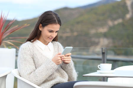 Portrait of a teenage girl checking her smart phone on a hotel terrace in winter