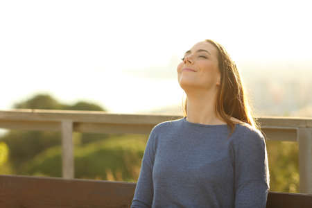 Woman sitting on a bench breathing fresh air in a park at sunset with a warm light