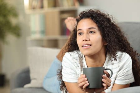 Pensive latin woman drinking coffee lying on a couch at home