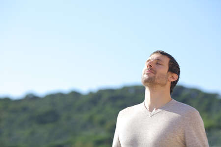 Homme détendu respirant l'air frais près des montagnes avec un ciel bleu en arrière-plan Banque d'images